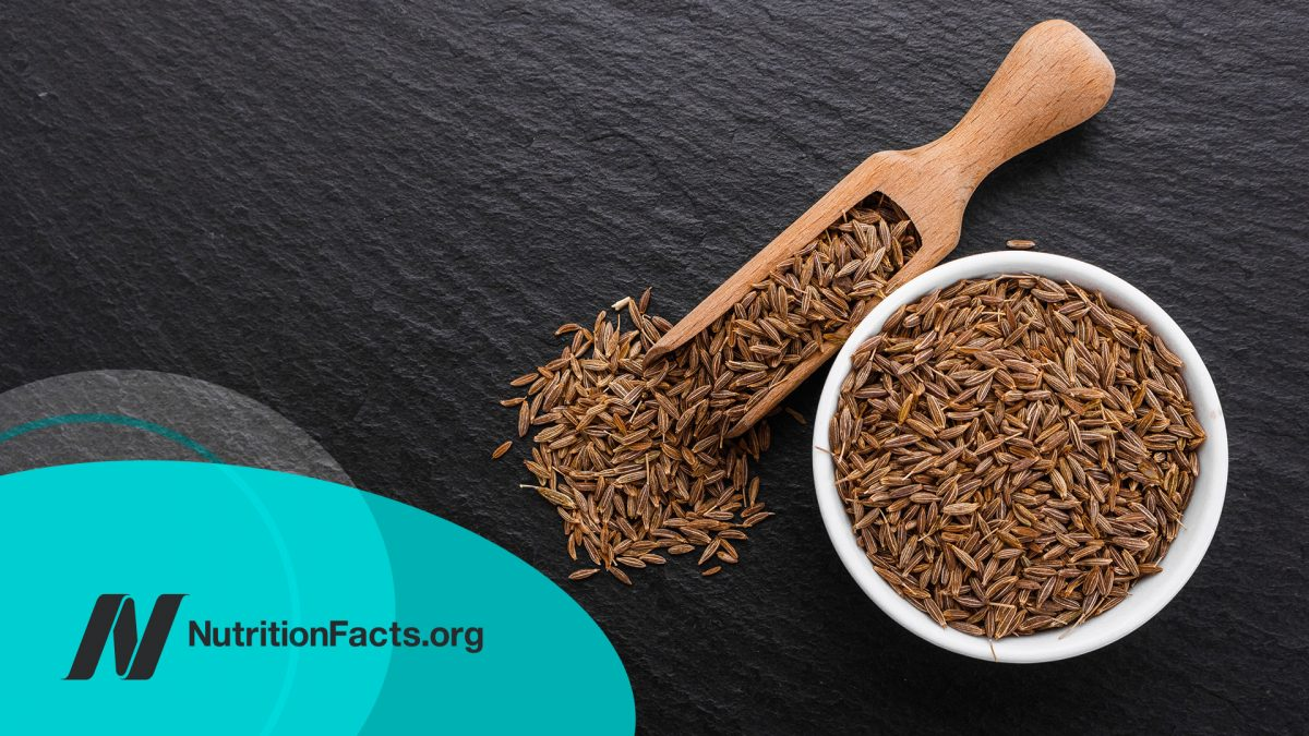 Cumin seeds in a bowl on a dark stone background
