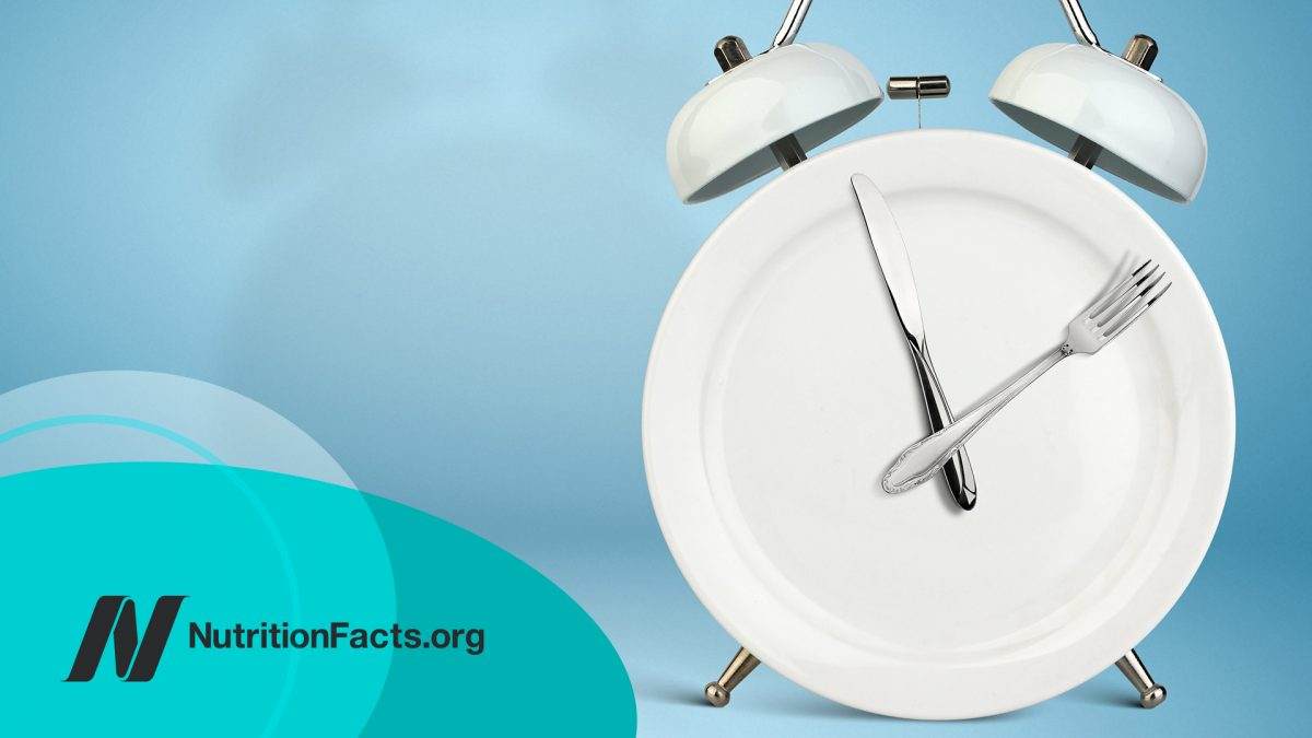 Plate as an Alarm clock with knife and fork as clock hands on blue background