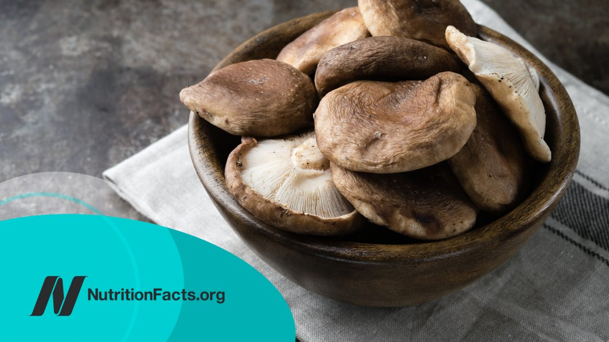 Wooden bowl with raw mushrooms on a dark background